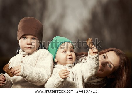 Woman and two sons playing in home garden - stock photo