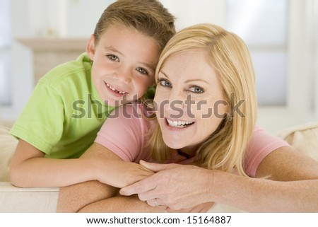 Woman and young boy sitting in living room smiling - stock photo