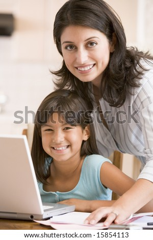 Woman and young girl in kitchen with laptop and paperwork smiling - stock photo