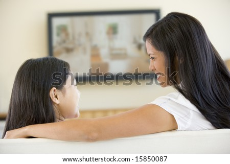 Woman and young girl in living room with flat screen television smiling - stock photo