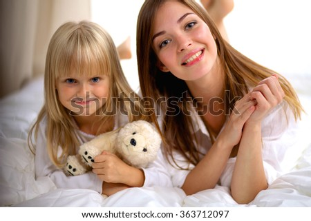 Woman and young girl lying in bed smiling - stock photo