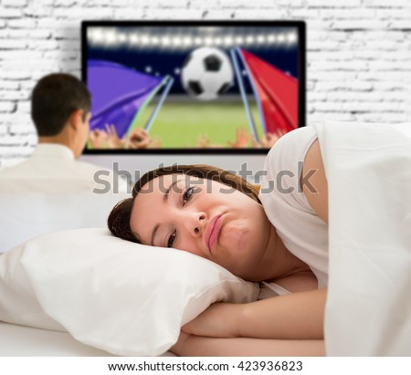 woman angry at being alone in bed and her husband is watching a football game tv - stock photo