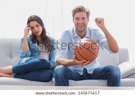 Woman annoyed by her partner watching basketball game in the living room - stock photo