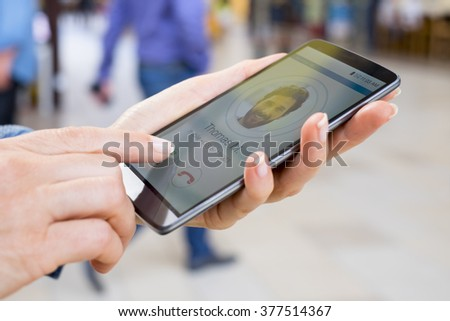 Woman answering mobile phone, calling a friend. Blur people background - stock photo