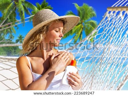 Woman applaying sun protection on skin. - stock photo
