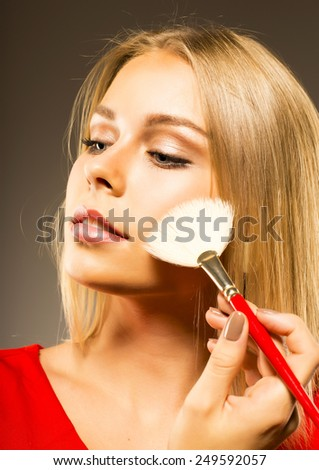 Woman applies cosmetics . Blond Hair. Daily Make-up - stock photo
