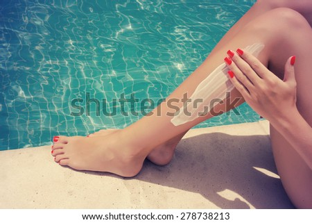 Woman apply cream on her smooth tanned legs - stock photo