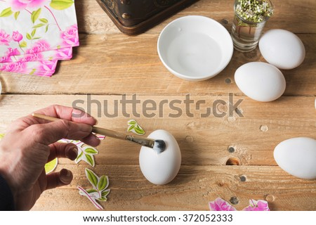 woman apply  glue on colored Easter egg, with the technique of decoupage - stock photo