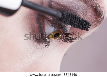 woman applying black mascara close-up, volume brush - stock photo