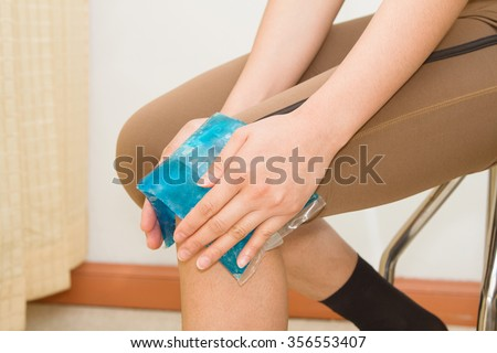 woman applying cold pack on swollen hurting knee after sport injury - stock photo