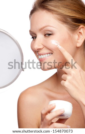 Woman applying cosmetic  cream on a clean fresh face - stock photo