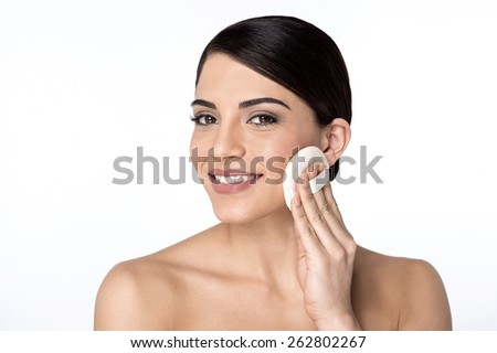 Woman applying cosmetic powder on face - stock photo