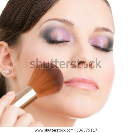 Woman applying cosmetics to her face with cosmetic brush, isolated on white - stock photo
