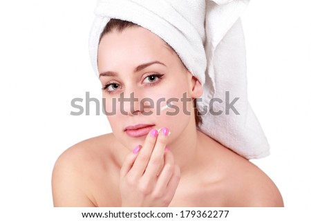 Woman applying cream on acne or skin blemishes - stock photo