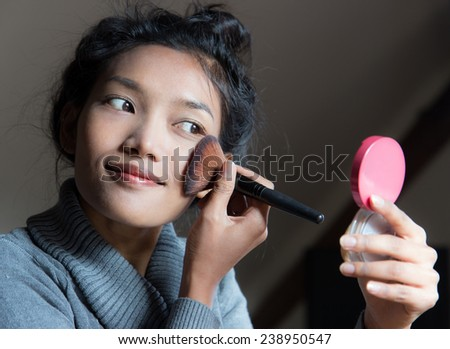 woman applying dry cosmetic on the face using makeup brush - stock photo
