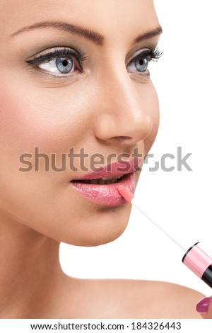 woman applying glossy on lips - stock photo