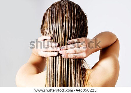Woman applying hair conditioner. Isolated on white. - stock photo