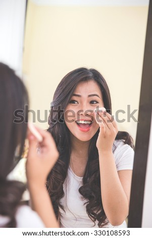 Woman applying make up into her face, putting on face powder - stock photo