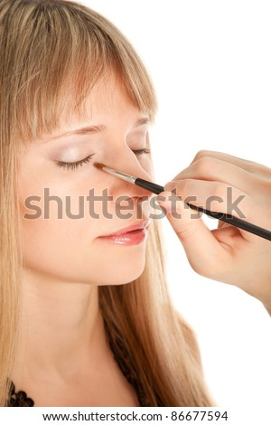 Woman applying makeup onto performer's face - stock photo