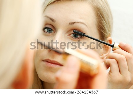 woman applying mascara in front of mirror - stock photo