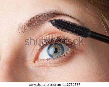 Woman applying mascara on her eyelashes - stock photo