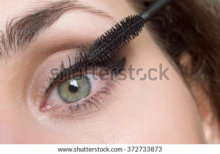 Woman applying mascara on her eyelashes - stock photo