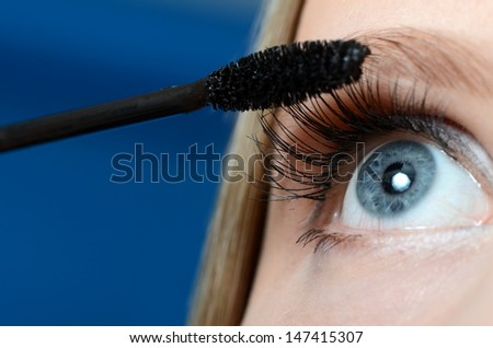 Woman applying mascara on her eyelashes  macro - stock photo