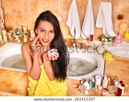 Woman applying moisturizer at bathroom. - stock photo