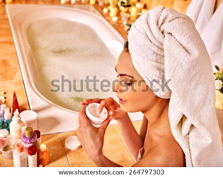 Woman applying moisturizer at bathroom. Towel on head. - stock photo