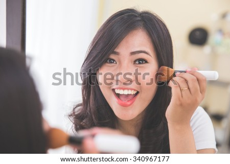 Woman applying on blush on, look at the mirror - stock photo