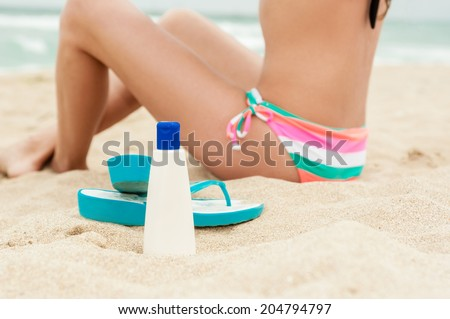 Woman applying sun protection lotion. Bottle of sun protection lotion and flip flops. Close-up, no face! - stock photo