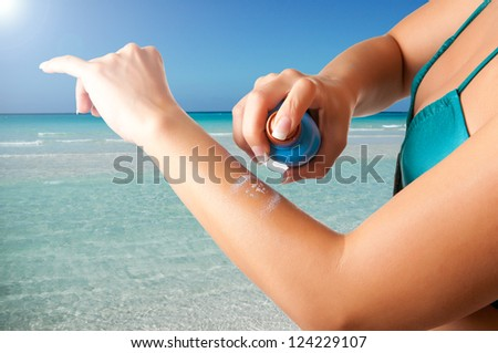 Woman applying sunscreen on her arm on a beach - stock photo