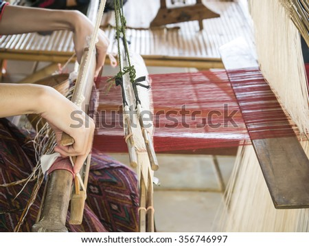 Woman are weaving silk by traditional way in Thailand - stock photo