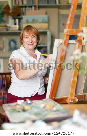 woman artist paints  on canvas in studio - stock photo