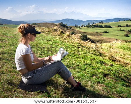Woman artist working outdoors on hillside - stock photo