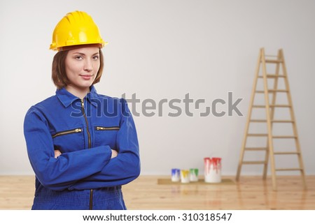 Woman as painter in empty room with ladder for renovation - stock photo