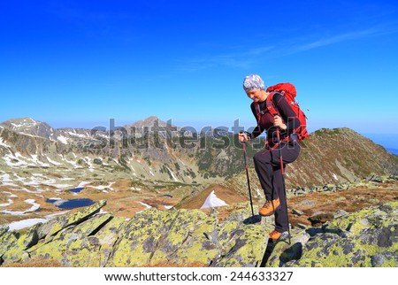 Woman ascending a rocky mountain trail in sunny summer day - stock photo