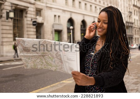 woman asking for directions on the phone with a map. - stock photo