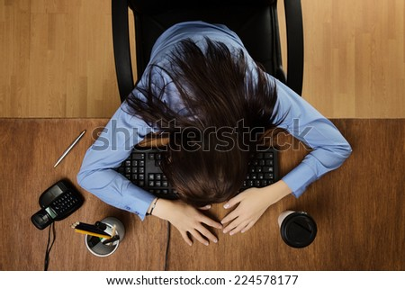 woman asleep at her desk taken from a birds eye view - stock photo