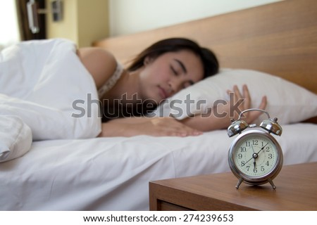 woman asleep in bed while her alarm shows the early time at home in bedroom - stock photo