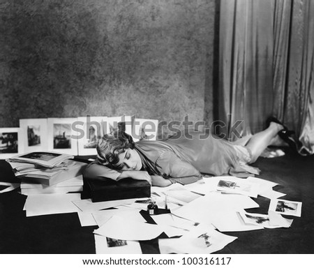 Woman asleep on floor surrounded by illustrations - stock photo