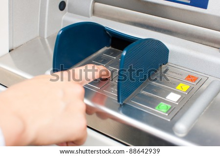 Woman at ATM or cash dispenser and is entering her PIN; only hand to be seen - stock photo