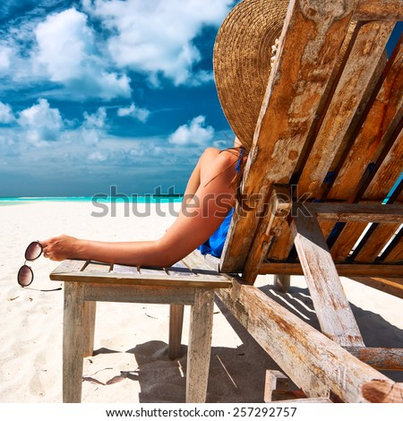 Woman at beautiful beach holding sunglasses - stock photo