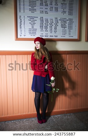Woman at bus station with rose at hand - stock photo