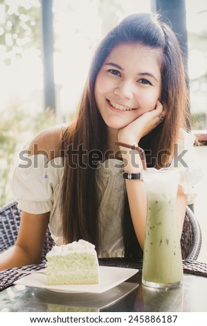 Woman at cafe thinking happy and smiling. Young beautiful Asian female model. Image is cross-processed giving retro style. - stock photo