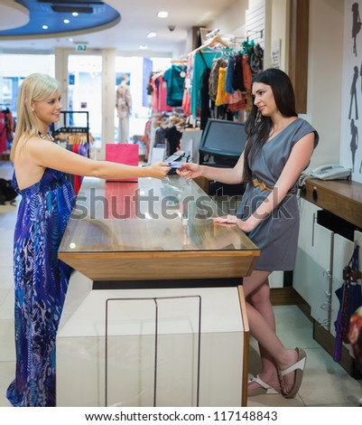 Woman at cash register paying with credit card in clothing store - stock photo