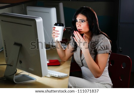 Woman at computer looks shocked. - stock photo