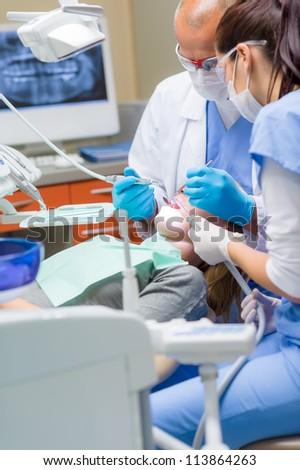 Woman at dentist surgery having dental checkup professional medical team - stock photo