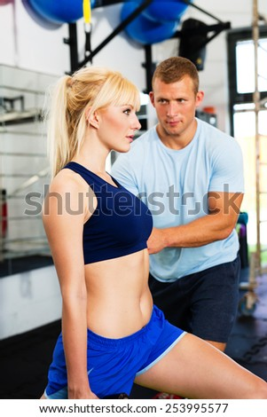 Woman at gym exercising with personal trainer - stock photo