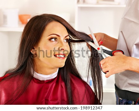 Woman at hairdresser with iron hair curler. - stock photo